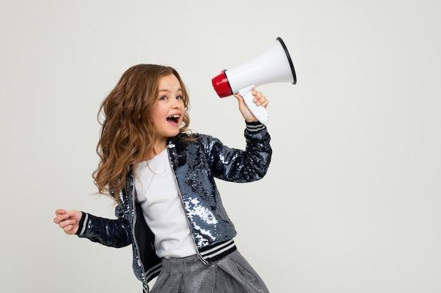 Linda chica adolescente europea con un megáfono informa las noticias sobre un fondo blanco puro