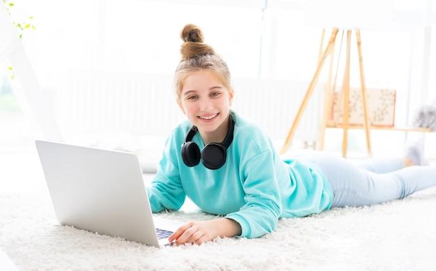 Linda chica adolescente con portátil tumbado en el suelo en la habitación de los niños