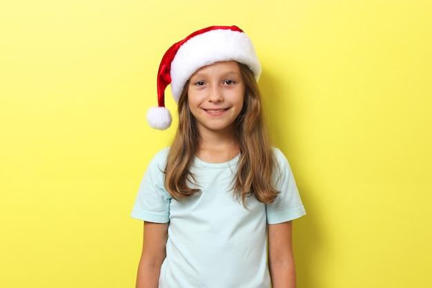 Linda chica alegre con un sombrero de navidad sobre un fondo de color sosteniendo un regalo