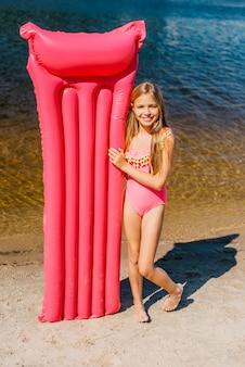 Linda chica con alfombra de aire de color en la orilla del mar
