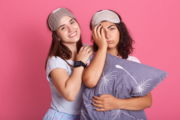 Linda chica amigas en traje de noche para una fiesta de pijamas sobre fondo rosa