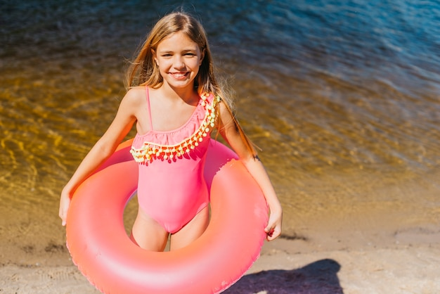 Linda chica con anillo de natación de color en la costa