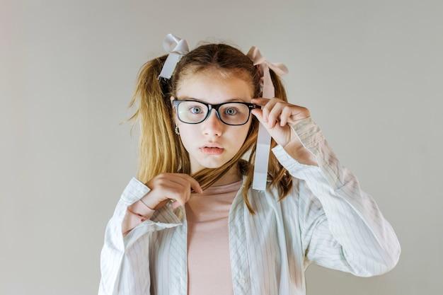 Linda chica en anteojos sosteniendo su cabello