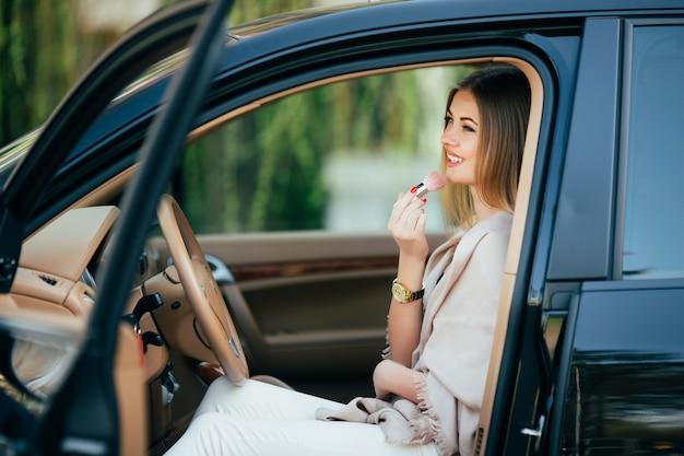 Linda chica aplicando lápiz labial en un coche
