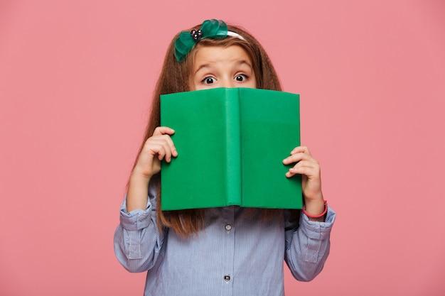 Linda chica con aro de pelo divirtiéndose mientras lee un libro interesante con los ojos bien abiertos