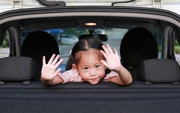 Linda chica asiática en un asiento trasero de un coche agitando adiós.