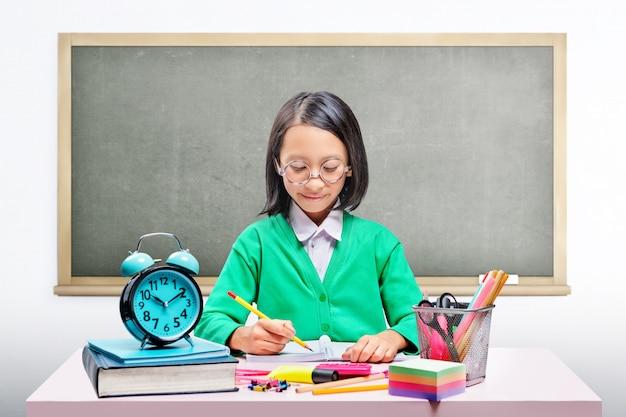 Linda chica asiática en gafas de aprendizaje con la escuela estacionaria en el escritorio