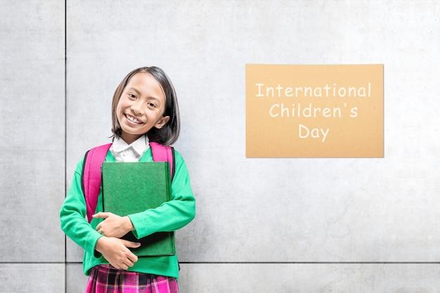 Linda chica asiática con una mochila sosteniendo el libro con una pared gris