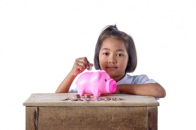 Linda chica asiática poniendo monedas en hucha aislado sobre fondo blanco.