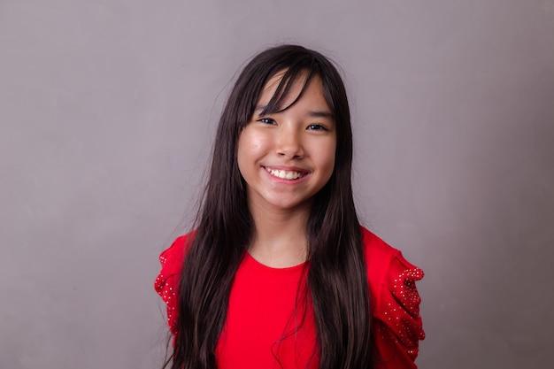 Linda chica asiática sonriendo mirando a cámara
