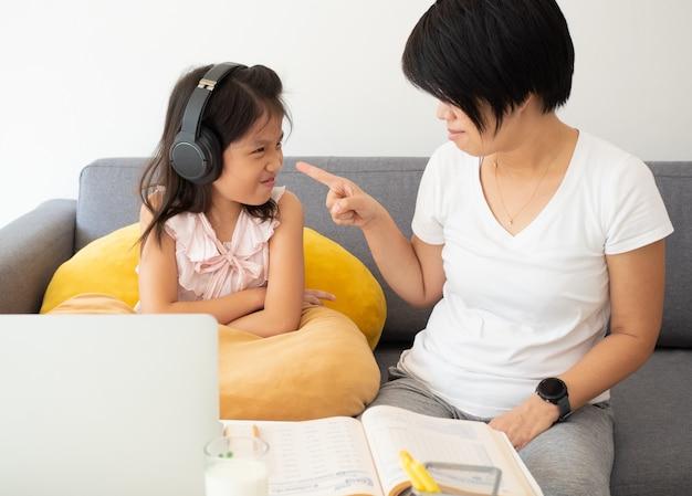 Linda chica asiática y su maestra usan un cuaderno para estudiar la lección en línea durante la cuarentena doméstica