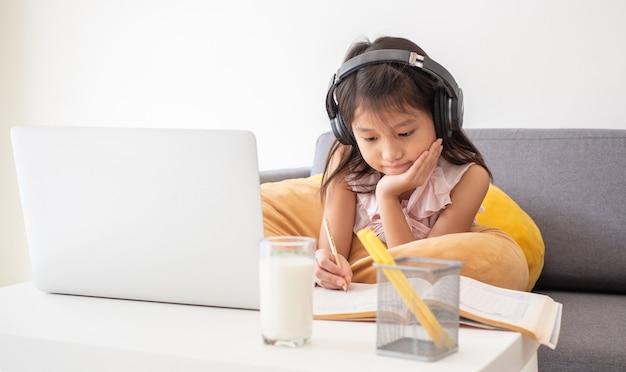Linda chica asiática usa la computadora portátil para estudiar la lección en línea durante la cuarentena en el hogar