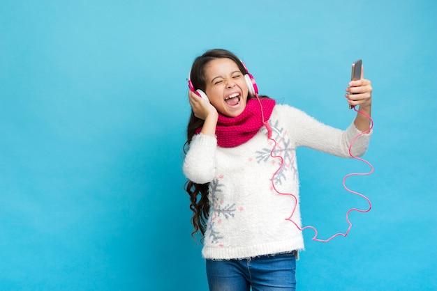 Linda chica con auriculares y teléfono inteligente en la mano