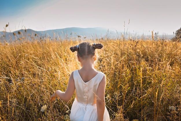 Linda chica bailando a través de un hermoso prado con trigo y flores en las montañas, vista posterior