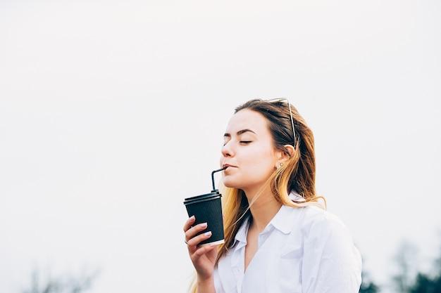 Una linda chica bebiendo un cóctel, sonriendo, con los ojos cerrados, copia espacio