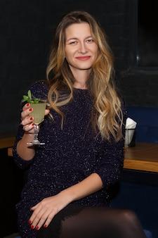 Linda chica bebiendo cócteles en el bar