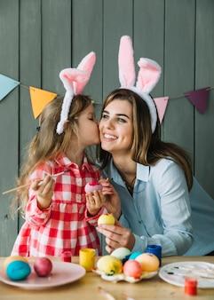 Linda chica besando a la madre en la mejilla mientras pinta huevos para pascua