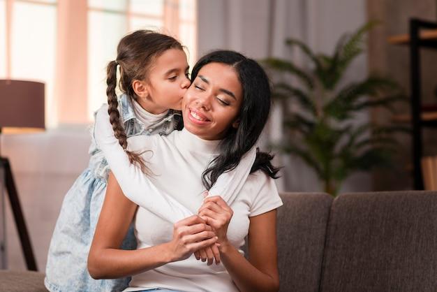 Linda chica besando a su madre en la mejilla