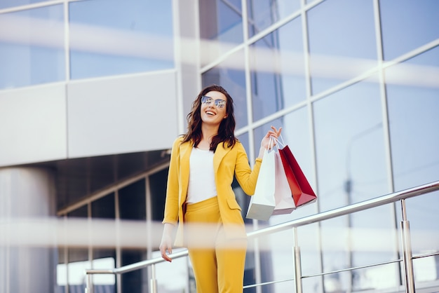 Linda chica con bolsa de compras en una ciudad