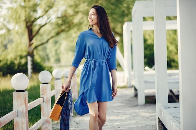 Linda chica con bolsa de compras en un parque