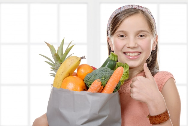 Linda chica con una bolsa llena de frutas y verduras