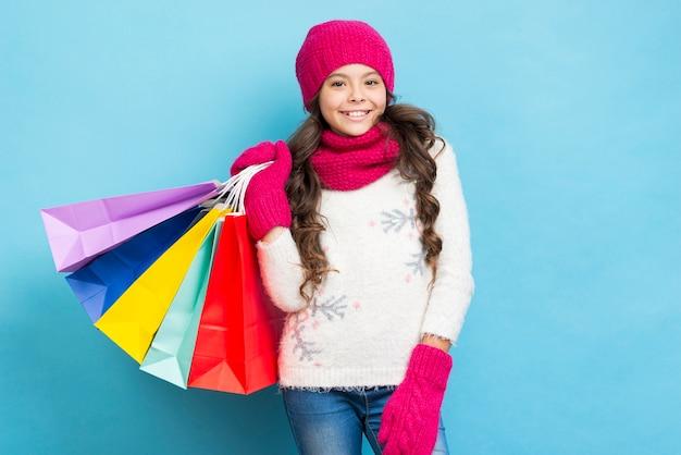 Linda chica con bolsas de compras en el hombro