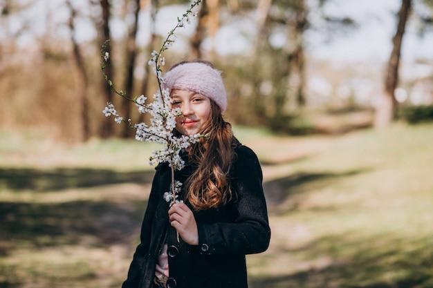 Linda chica con brench floreciente en el parque