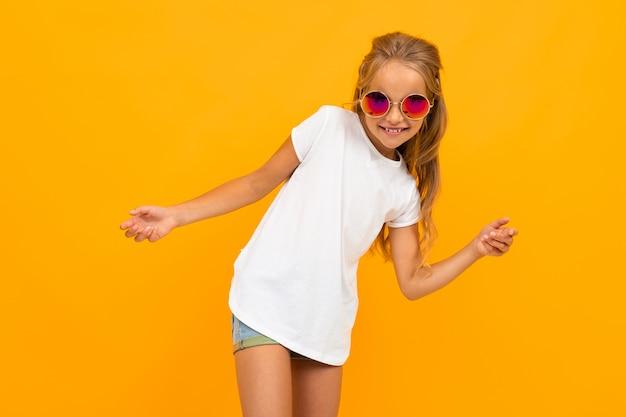 Linda chica brillante con gafas en una camiseta con un diseño en una pared naranja