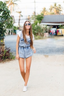 Linda chica bronceada delgada de pie cerca de un árbol en un parque. viste camiseta blanca, pantalones cortos de mezclilla, zapatillas blancas y gafas de sol negras.