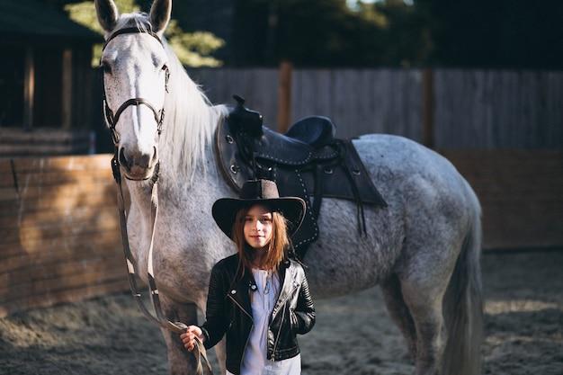 Linda chica con caballo en el rancho