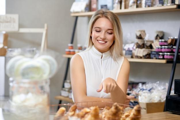 Linda chica con cabello rubio comprar croissants en tienda local.