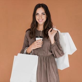 Linda chica con café y muchas redes de compras sonriendo a la cámara