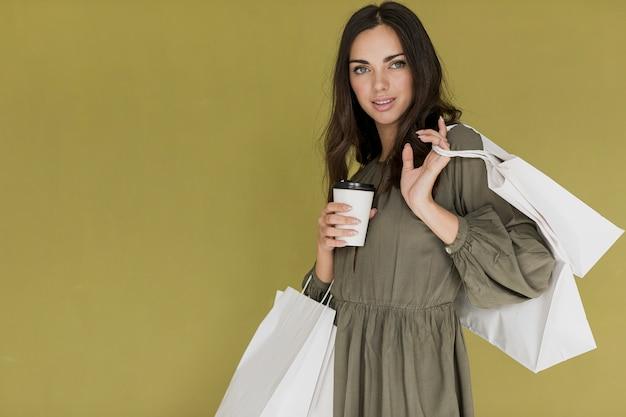 Linda chica con café y muchas redes de compras