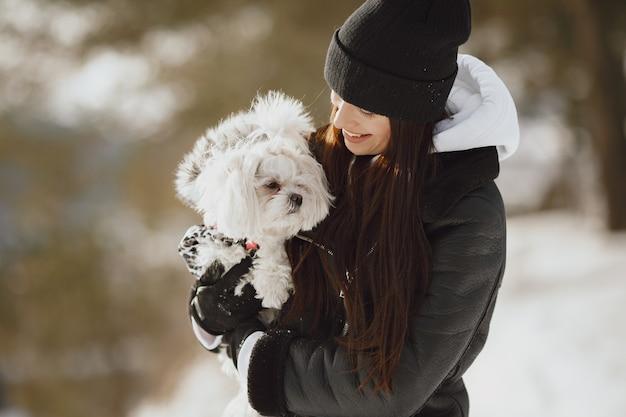 Linda chica caminando en un parque de invierno. mujer con chaqueta marrón. dama con un perro.