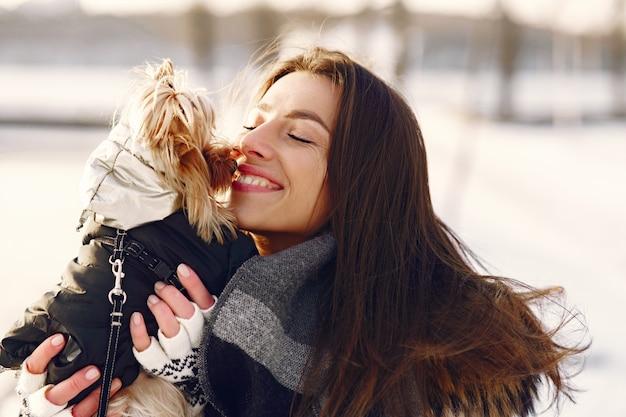 Linda chica caminando en un parque de invierno con su perro
