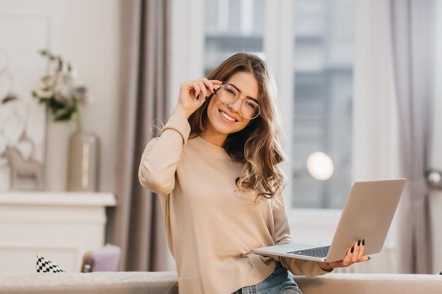 Linda chica en camisa beige tocando gafas y sosteniendo portátil con sonrisa