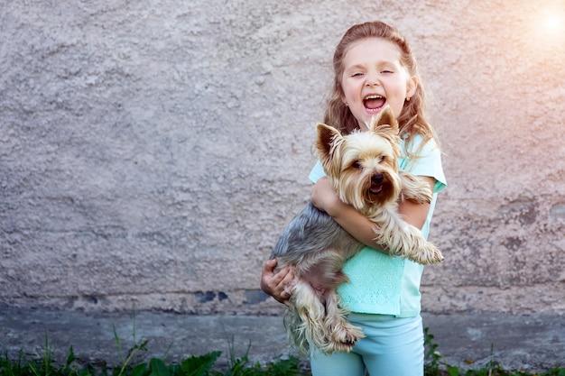 Una linda chica en una camiseta azul con hoyuelos en sus mejillas sosteniendo un perro y sonriendo