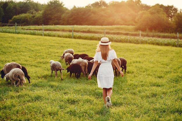 Linda chica en un campo con cabras