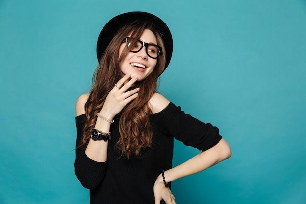 Linda chica casual con sombrero y gafas mirando a otro lado