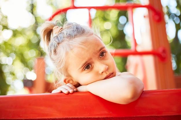 Linda chica caucásica aburrido jugar solo en el parque al aire libre en verano