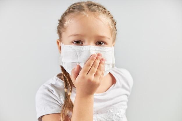 Linda chica caucásica en una máscara médica