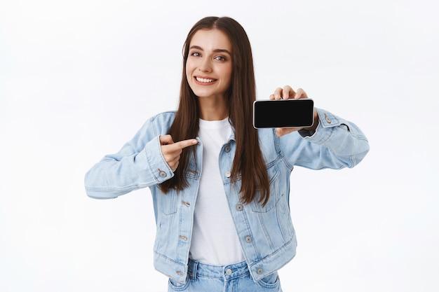 Linda chica caucásica moderna saliente en chaqueta de mezclilla, sosteniendo el teléfono inteligente horizontalmente, mostrando y señalando la pantalla del móvil, sonriendo complacida, dar consejos descargar la aplicación, fondo blanco