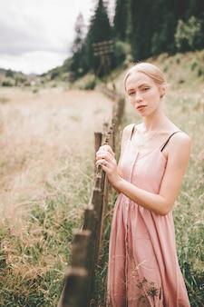 Linda chica caucásica relajante en la naturaleza con su mano sobre la valla de madera.
