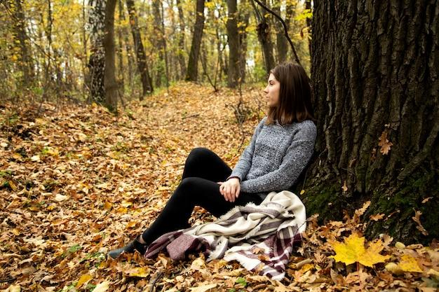 Linda chica en una chaqueta gris sentada en el bosque de otoño en una hoja amarilla cerca de un árbol grande