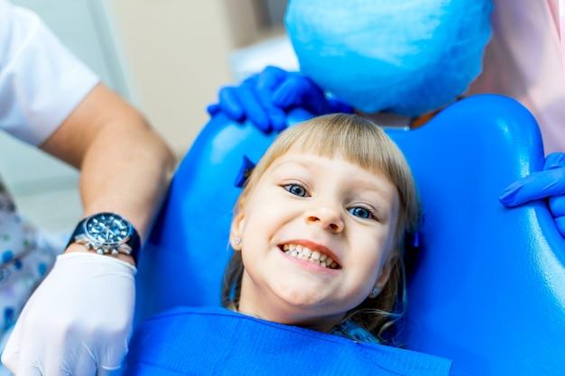 Linda chica en clínica dental. niño en armario estomatológico con boca abierta.