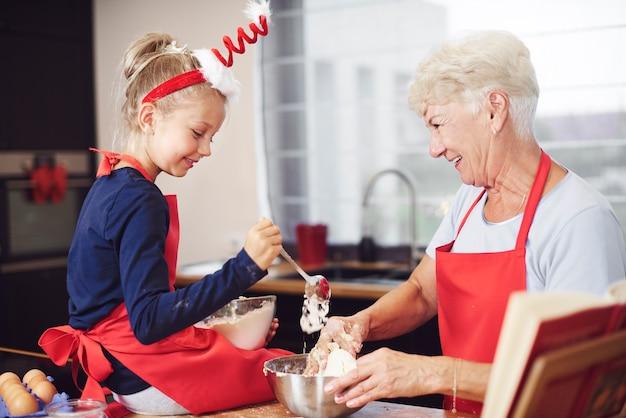 Linda chica cocinando con la ayuda de su abuela