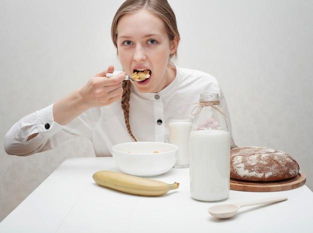 Linda chica comiendo cereales con leche