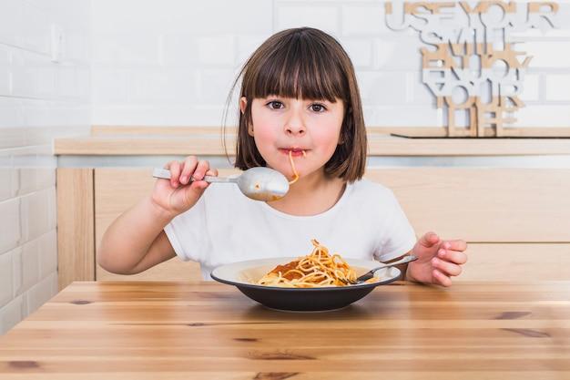 Linda chica comiendo deliciosos espaguetis