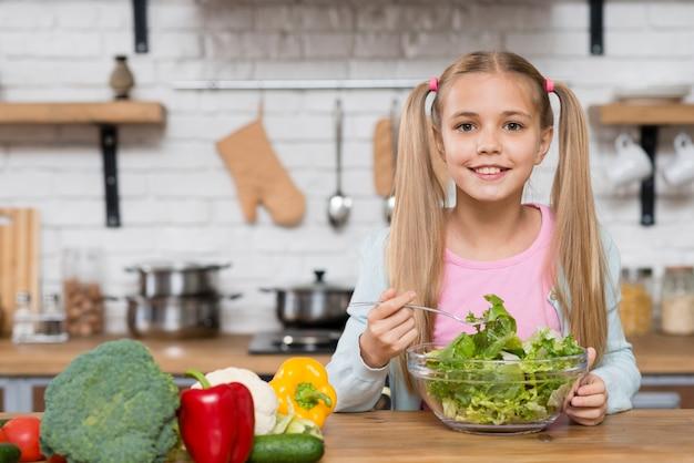Linda chica comiendo ensalada en la cocina