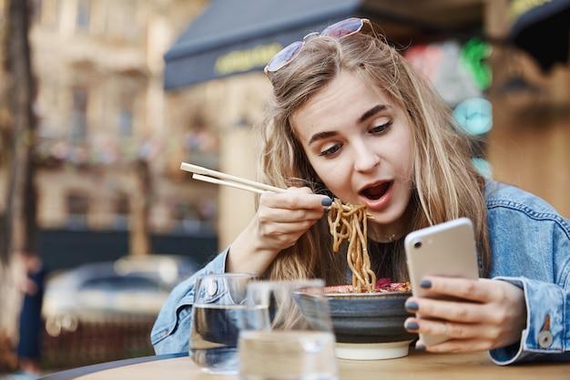 Linda chica comiendo fideos chinos y mirando el teléfono, sosteniendo c
